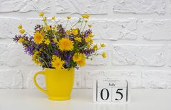 Деревянный календарь 5-ое июля кубов и желтая чашка с яркими покрашенными цветками против белой кирпичной стены Дата календаря ша стоковая фотография rf