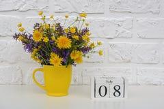 Деревянный календарь 8-ое июля кубов и желтая чашка с яркими покрашенными цветками против белой кирпичной стены Дата календаря ша стоковое фото rf