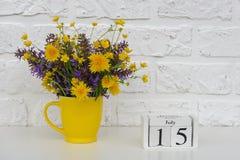 Деревянный календарь 15-ое июля кубов и желтая чашка с яркими покрашенными цветками против белой кирпичной стены Календарь шаблон стоковые фото