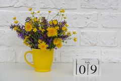 Деревянный календарь 9-ое июля кубов и желтая чашка с яркими покрашенными цветками против белой кирпичной стены Дата календаря ша стоковое изображение rf