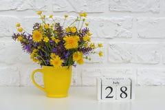 Деревянный календарь 28-ое июля кубов и желтая чашка с яркими покрашенными цветками против белой кирпичной стены Дата календаря ш стоковая фотография rf