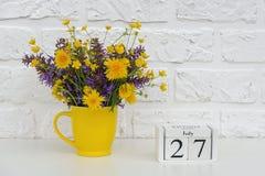 Деревянный календарь 27-ое июля кубов и желтая чашка с яркими покрашенными цветками против белой кирпичной стены Дата календаря ш стоковые фотографии rf