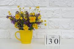 Деревянный календарь 30-ое июля кубов и желтая чашка с яркими покрашенными цветками против белой кирпичной стены Дата календаря ш стоковые фото