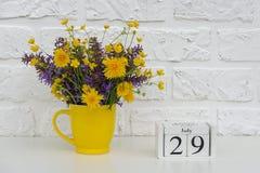 Деревянный календарь 29-ое июля кубов и желтая чашка с яркими покрашенными цветками против белой кирпичной стены Дата календаря ш стоковое изображение rf
