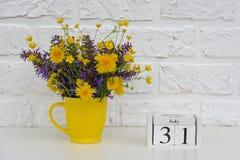 Деревянный календарь 31-ое июля кубов и желтая чашка с яркими покрашенными цветками против белой кирпичной стены Дата календаря ш стоковое изображение