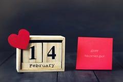 Деревянный календарь с датой 14-ое февраля, бумажного сердца и подарка На темной деревянной предпосылке с космосом экземпляра Стоковая Фотография