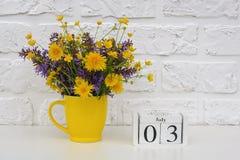 Деревянный календарь 3-ье июля кубов и желтая чашка с яркими покрашенными цветками против белой кирпичной стены Дата календаря ша стоковые фотографии rf