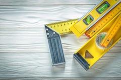 Деревянный квадрат попытки уровня конструкции метра на верхней части VI белой доски Стоковые Фото