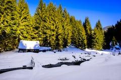Деревянный коттедж на речном береге в зиме Стоковые Фотографии RF