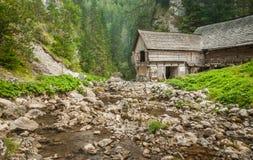 Деревянный коттедж в горах с заводью Стоковые Изображения RF