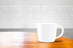Деревянный круглый стол с белой кружкой на комнате плитки кирпича Стоковые Фотографии RF
