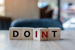 Деревянный куб с сальто над блоком ДОН t для того чтобы СДЕЛАТЬ слово ИТ на предпосылке таблицы успех, стратегия, решение, дело и стоковые изображения