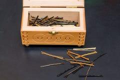 Деревянный ларец с незримым и hairpins на черной таблице в ha Стоковая Фотография RF