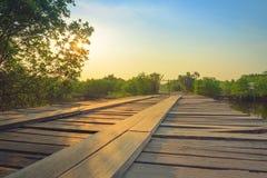 Деревянный мост в сельской местности пересекая реку на заход солнца Стоковая Фотография