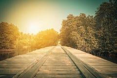 Деревянный мост в сельской местности пересекая реку на заход солнца Стоковые Фото