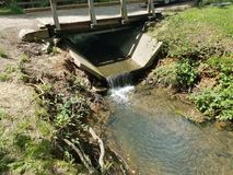 Деревянный мост и малый поток с цементом стоковые изображения