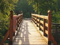 Деревянный мост на первых sunrays на утре Стоковые Фото