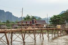 Деревянный мост над песней реки к дому для гостей берега реки Стоковые Изображения