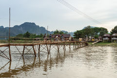 Деревянный мост над песней реки к дому для гостей берега реки Стоковая Фотография