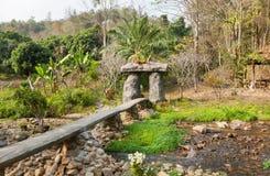 Деревянный мост над рекой в старой тайской деревне с деревьями вокруг Стоковые Изображения RF