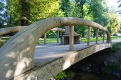 Деревянный мост с изогнутыми рельсами через малое реку в парке стоковые фотографии rf