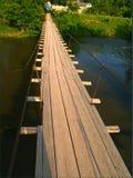 Деревянный мост через реку: доски светлого песка красят пригвозженный до одно другое руководство через реку, перила от утюга ca Стоковое фото RF