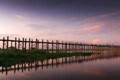 Деревянный мост teak u Bein накаляя на заходе солнца Стоковая Фотография
