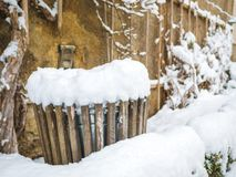 Деревянный мусорный бак покрытый с снегом в стене предпосылки сезона зимы Австрии Зальцбурга mirabellplatz стоковая фотография