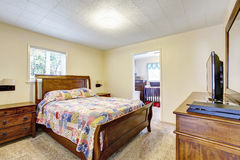 Деревянный обеспеченный интерьер спальни с славными постельными принадлежностями и телевизором Стоковое Изображение RF