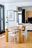 Деревянный обеденный стол с белыми стульями стоковое изображение