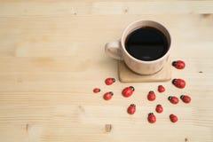 Деревянный обеденный стол с черным кофе и красным ladybug Стоковое Изображение RF