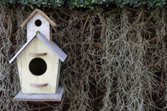 Деревянный дом птицы на сухой траве и зеленой предпосылке лист стоковое изображение