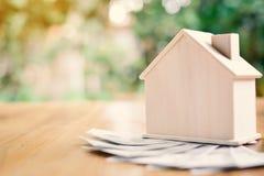 Деревянный дом с деньгами доллара на предпосылке bokeh дерева таблицы Стоковое фото RF