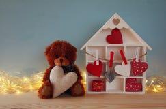 Деревянный дом с много сердцами и милого плюшевого медвежонка Стоковое фото RF