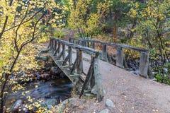 Деревянный пешеходный мост над потоком Стоковые Изображения