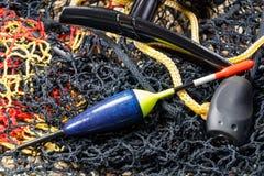 Деревянный поплавок рыбной ловли с вьюрком рыболовной удочки и садок для рыбы на каменистой земле стоковое изображение