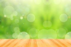 Деревянный пол и абстрактная зеленая предпосылка bokeh Стоковая Фотография