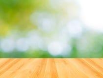 Деревянный пол и абстрактная зеленая предпосылка bokeh Стоковые Изображения
