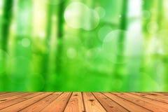 Деревянный пол и абстрактное зеленое bokeh предпосылки дерева Стоковое Изображение