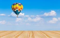 Деревянный пол и горячий воздушный шар на голубом небе Стоковое Изображение