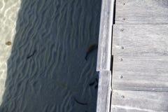 Деревянный променад на прозрачной морской воде с песком на дне стоковые фотографии rf