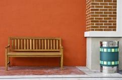 Деревянный стенд против пустой стены и зеленой погани. Стоковая Фотография