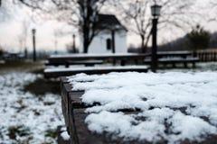 Деревянный стол в саде покрытом снегом, лампами и малой церковью в предпосылке стоковые изображения