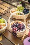 Деревянный стол и украшение партии пикника с корзинами плодоовощ: виноградины, персики, сливы на солнечный летний день стоковая фотография rf