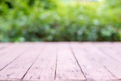 Деревянный стол перед абстрактной предпосылкой запачканной природой стоковое изображение