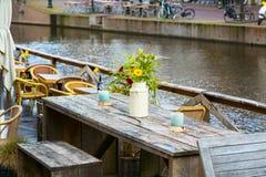 Деревянный стол кафа с цветками в взгляде вазы и канала Стоковое Изображение RF
