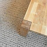 Деревянный стол на ковре связанном серым цветом стоковые фотографии rf
