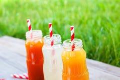 Деревянный стол сока цвета плодоовощ бутылок различный Стоковая Фотография RF
