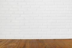Деревянный стол с запачканной белой стеной birck на предпосылке Стоковое Изображение RF