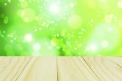 Деревянный стол с зеленым bokeh стоковые фотографии rf